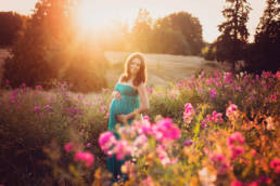 pregnant woman in field of sweet peas with sun setting behind her