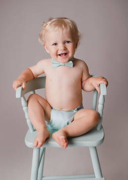 one year old baby in antique high chair wearing an aqua bow tie and diaper cover
