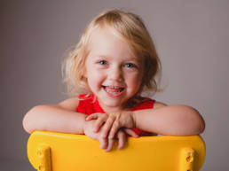 Two year old girl sitting backwards on a bright yellow chair smiles at the camera with arms posed folded across the back of the chair