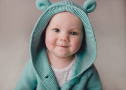 6 month old baby wearing aqua knit hoodie with animal ears