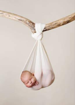 newborn baby asleep in sling tied to tree branch