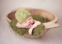 newborn baby wearing green knit hat in wooden trencher bowl