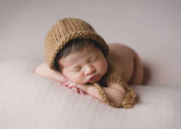 newborn baby wearing knit bonnet posed on tummy with chin on hands