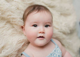 6 month old baby with big brown eyes posed on faux fur, stares into camera